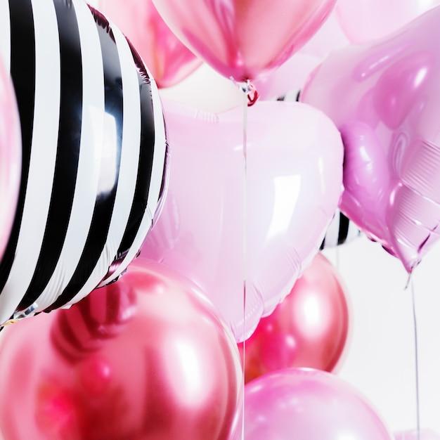 Set di palloncini a forma di cuore e tondo rosa e strisce su sfondo chiaro con spazio di copia. Foto Premium
