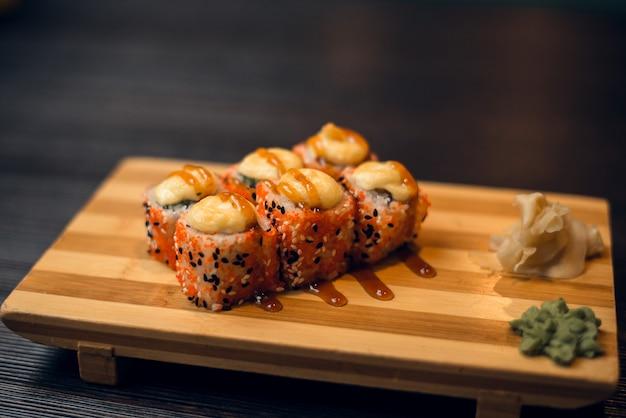 Set di panini caldi al forno su un vassoio di legno con zenzero e wasabi. gustosi sushi in un ristorante cinese Foto Premium