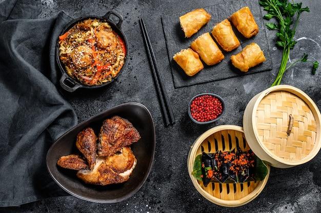 Set di piatti di cucina cinese, sfondo nero di cibo. tagliatelle cinesi, gnocchi, anatra alla pechinese, dim sum, involtini primavera. famoso. vista dall'alto Foto Premium