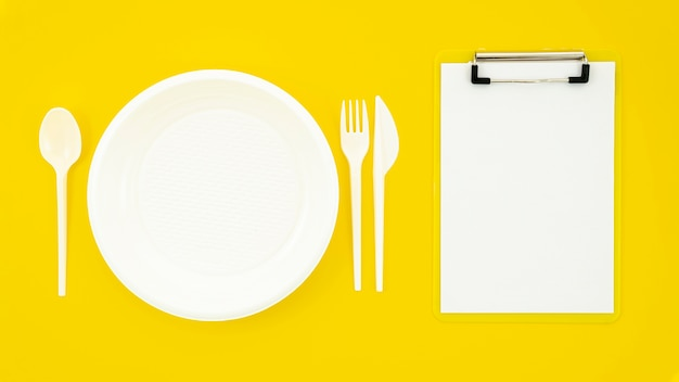Set di piatto bianco e appunti su sfondo giallo Foto Gratuite