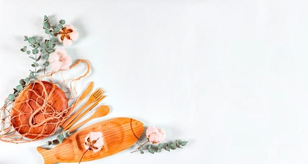 Set di posate in legno naturale eco, piatto, rete a sacco, foglie di eucalipto e fiori di cotone su fondo pastello. Foto Premium