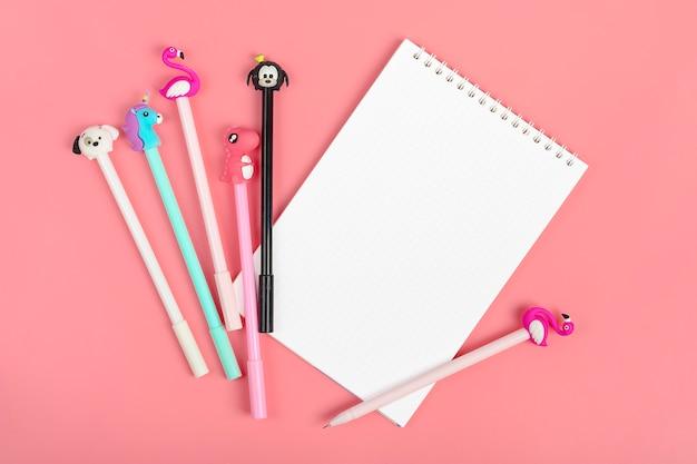 Set di quaderni per appunti e penne su sfondo rosa Foto Premium