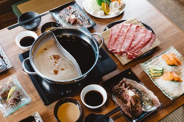 Set di shabu tra cui fette rari di manzo wagyu a5, shabu shoyu e base trasparente, salmone, sushi. Foto Premium