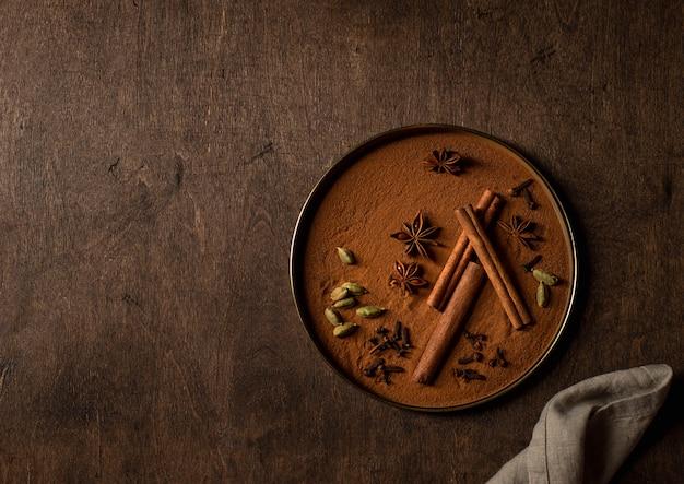 Set di spezie, cannella, cardamomo, anice stellato, superficie in legno di chiodi di garofano Foto Premium