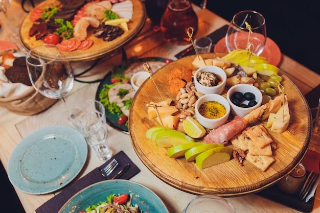 Set di spuntini italiani di antipasti. brushette, varietà di formaggio, olive mediterranee, sottaceti, prosciutto di parma con melone Foto Premium