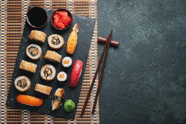 Set di sushi e maki sul tavolo di pietra scura. vista dall'alto con lo spazio della copia. distesi. Foto Premium