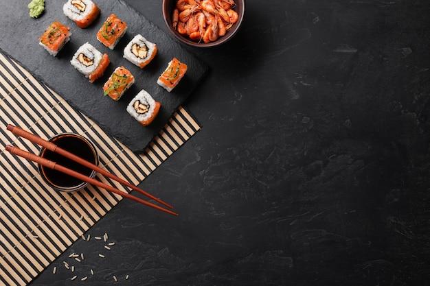Set di sushi e maki sul tavolo di pietra. vista dall'alto con lo spazio della copia Foto Premium