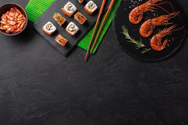 Set di sushi, gamberetti e maki con una bottiglia di vino sul tavolo di pietra. vista dall'alto con lo spazio della copia Foto Premium
