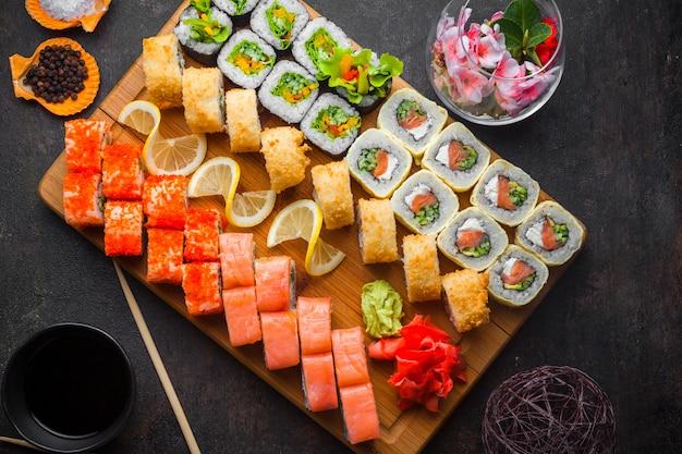 Set di sushi vista dall'alto con salsa di soia e bacchette in tavola di legno Foto Gratuite