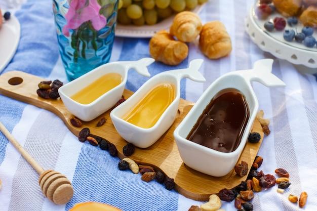 Set di tre salsa bianca con miele dolce sul vassoio di legno al momento del cibo da picnic Foto Premium