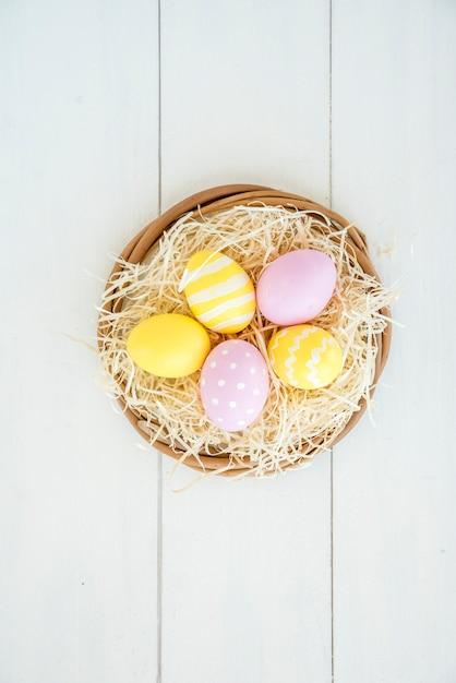 Set di uova luminose nel nido decorativo Foto Gratuite