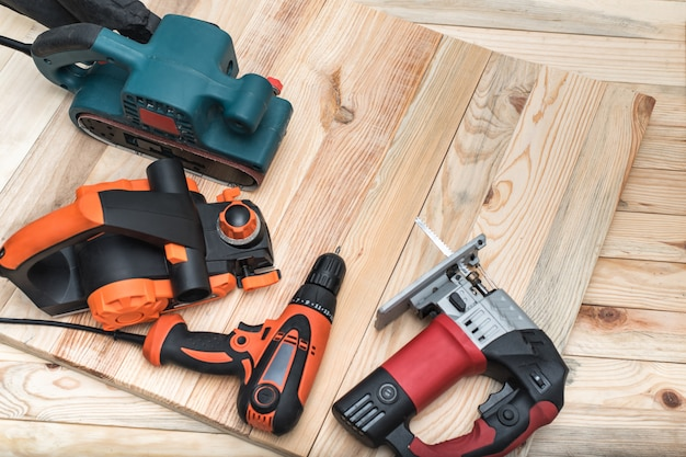 Set di utensili elettrici portatili per la lavorazione del legno su legno chiaro. avvicinamento Foto Premium