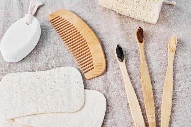 Set naturale per il bagno di spazzolini da denti in bambù, luffa spongle e spazzola per capelli in legno su uno sfondo di lino. Foto Premium