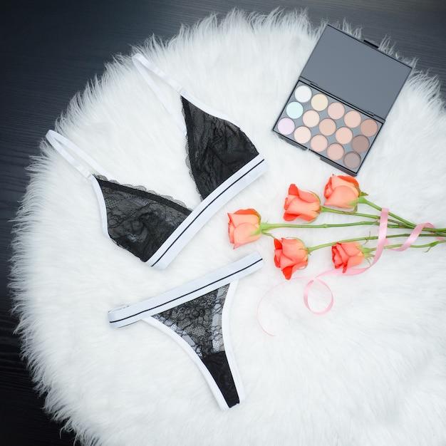 Set nero di biancheria intima di pizzo su pelliccia bianca. rose arancio e ombretto. concetto alla moda Foto Premium