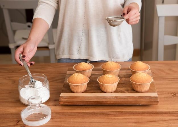 Setaccio della tenuta della donna che prepara spruzzare i muffin con lo zucchero Foto Gratuite