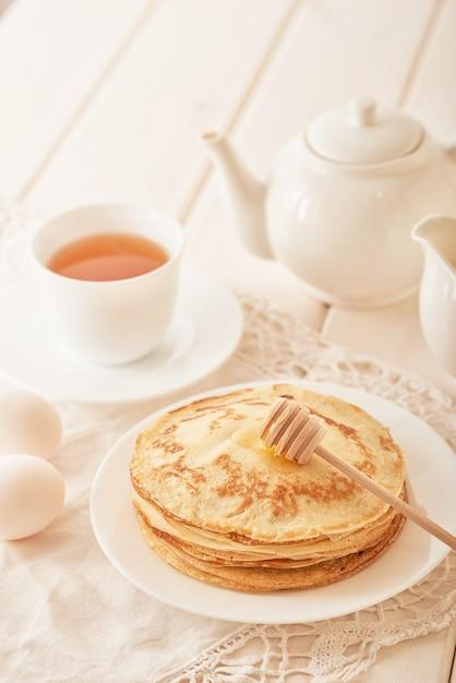 Settimana del pancake: pancake con miele e tè sul tavolo Foto Premium