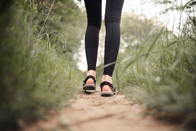 Sezione bassa dei piedi della viandante femminile che cammina sulla pista Foto Gratuite