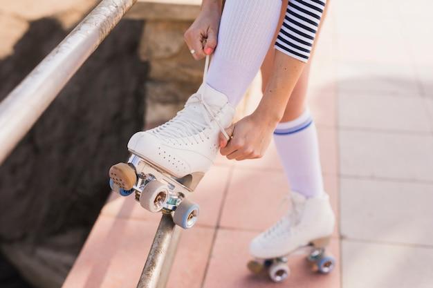 Sezione bassa della donna che lega il merletto del pattino a rotelle Foto Gratuite
