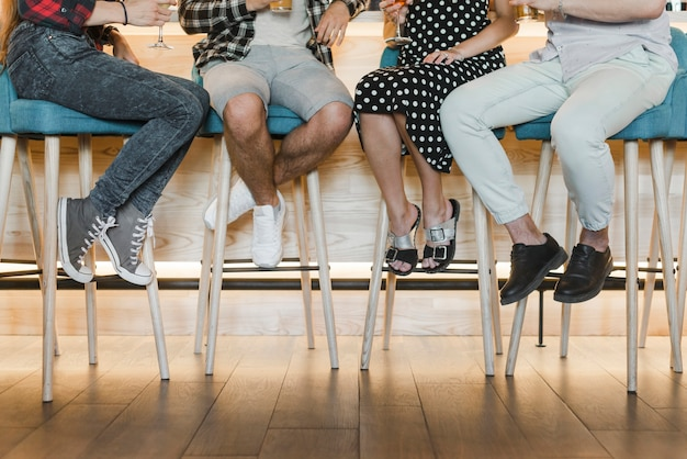 Sezione bassa di amici seduti su sgabelli da bar scaricare foto