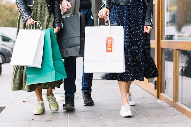 Sezione bassa di un amici che camminano sul marciapiede con borse della spesa colorate Foto Gratuite