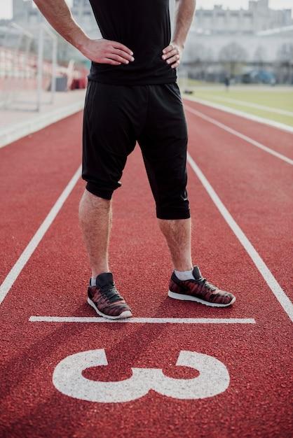 Sezione bassa di un atleta maschio sulla linea di partenza della pista con il numero tre Foto Gratuite