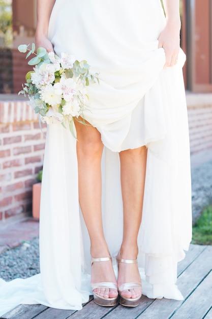 Sezione bassa di un bouquet di fiori della holding della sposa in mano mostrando i suoi tacchi alti alla moda Foto Gratuite