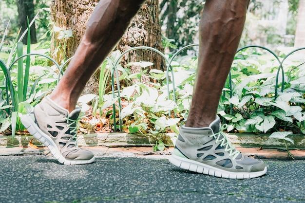 Sezione bassa di un giovane atleta piedi maschili in giardino Foto Gratuite