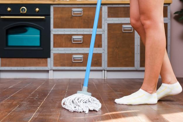 Sezione bassa di un pavimento di pulizia più pulito in cucina Foto Gratuite