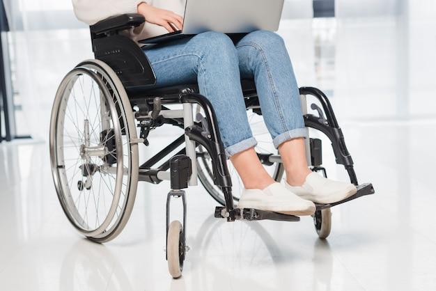 Sezione bassa di una donna disabile che si siede sulla sedia a rotelle facendo uso della compressa digitale Foto Gratuite