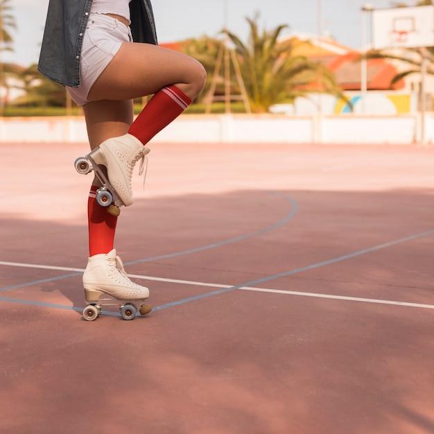 Sezione bassa di una pattinatrice in piedi su una gamba sopra la corte Foto Gratuite