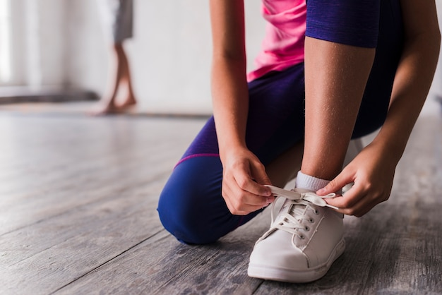 Sezione bassa di una ragazza che lega il laccio delle scarpe bianche Foto Gratuite
