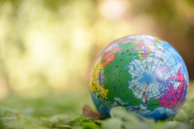 Sfera del globo sulle foglie verdi naturali a terra e sul fondo verde del bokeh. concetto di giornata mondiale dell'ambiente. Foto Premium