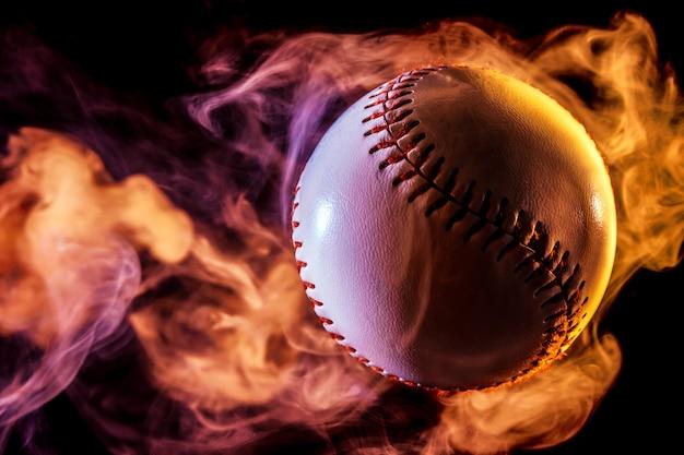 Sfera di baseball bianca in fumo rosso multi-coloured da un vape su una priorità bassa isolata nera Foto Premium