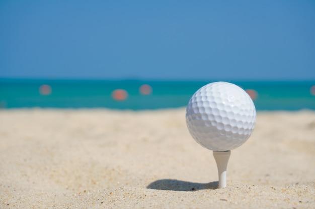 Sfera di golf sulla sabbia della spiaggia nell'ambito della priorità bassa del cielo blu Foto Premium