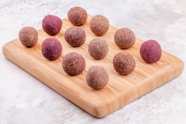 Sfere crude casalinghe di energia del cacao del vegano sul vassoio di legno Foto Premium