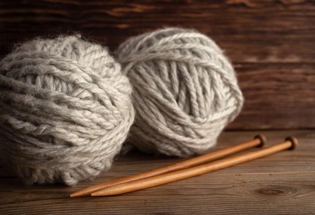 Sfere di filato e ferri da maglia su un fondo di legno. Foto Premium