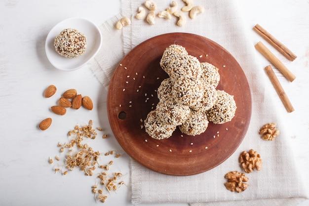 Sfere di sfere energetiche con mandorle, sesamo, anacardi, noci, datteri e grano germinato, vista dall'alto, copia spazio. Foto Premium