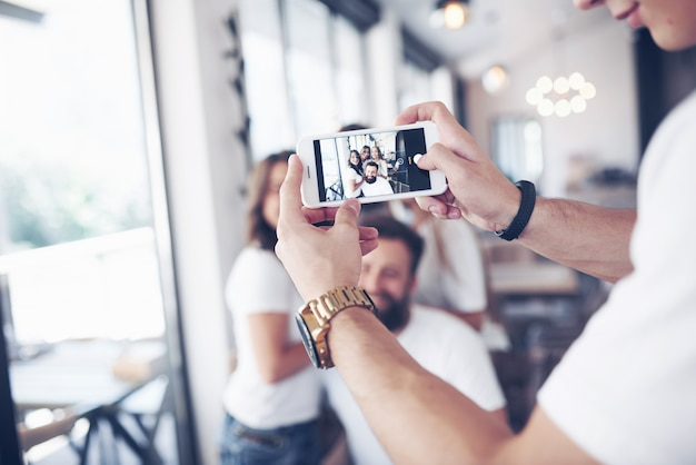 Sfocatura ritratto di giovani migliori amici beati con le mani che tengono il telefono in primo piano Foto Premium