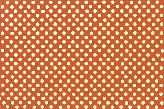 Sfondo arancione chiaro da carta da imballaggio con una di pois dorati Foto Premium