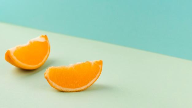 Sfondo blu con fettine di mandarino tagliate Foto Gratuite