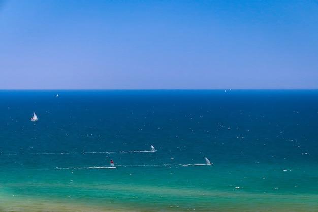 Sfondo del mare con piccole barche e yacht a vela, pratica del windsurf Foto Premium