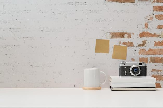 Sfondo di area di lavoro con macchina fotografica d'epoca, film, libri e copia spazio Foto Premium