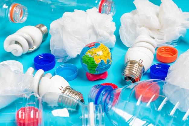 Sfondo di bottiglie di plastica trasparente, sacchetti di plastica, fluorescenti, globo. distesi Foto Premium