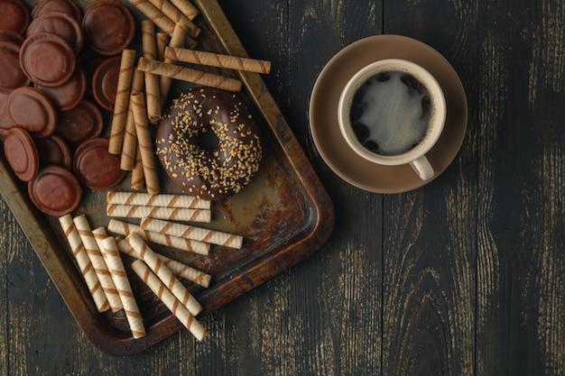 Sfondo di cioccolatini. cioccolato. tazza di cioccolata calda, limone, noci e assortimento di cioccolatini pregiati nel buio e cioccolato al latte sul tavolo di legno scuro Foto Premium