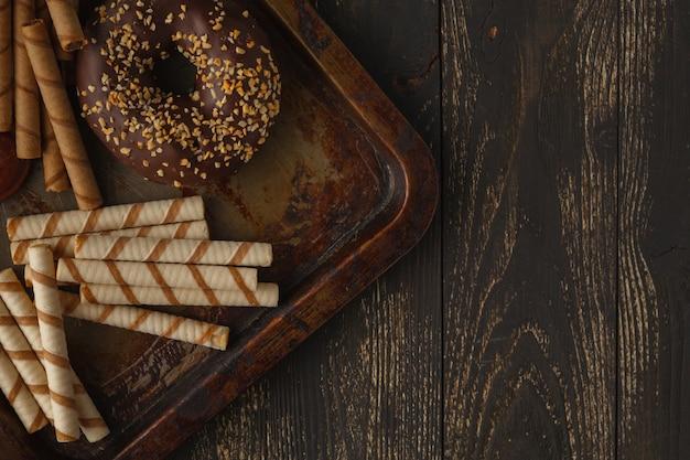 Sfondo di cioccolatini. limone, noci, biscotti e assortimento di cioccolatini pregiati in cioccolato fondente e al latte su sfondo scuro. Foto Premium