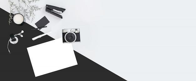 Sfondo di colore bianco e nero con rami di fiori, una tazza, auricolare, penna, spillatrice, macchina fotografica, carta di nome. Foto Premium