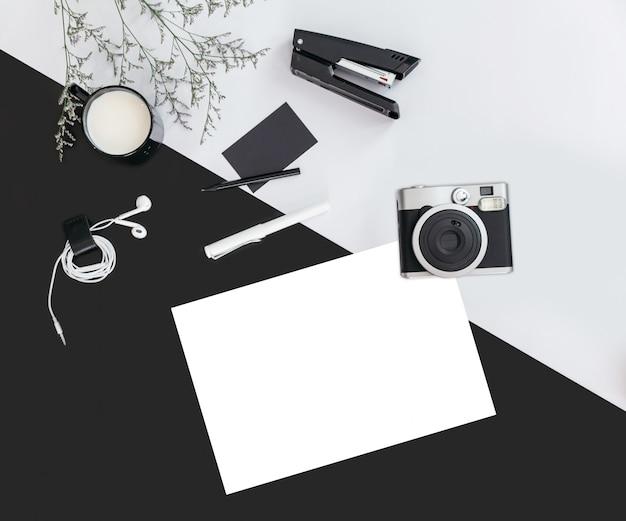 Sfondo di colore nero e grigio con rami di fiori, una tazza di latte, auricolare, penna, pinzatrice, fotocamera, carta di nome e carta bianca. vista dall'alto Foto Premium