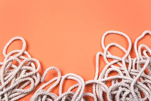 Sfondo di corda di cotone bianco minimalista con trama e contrasto su sfondo corallo luminoso. Foto Premium