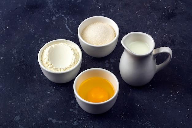 Sfondo di cottura. ingredienti per la cottura del dolce in ciotole sul tavolo scuro. concetto di cibo. avvicinamento Foto Premium