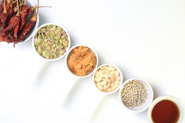 Sfondo di erbe tailandesi con dries peperoncino, pepe, citronella, aglio, zucchero di cocco e salsa di pesce Foto Premium